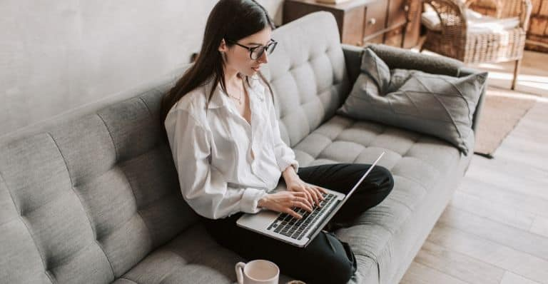 person sitting on her couch working from home